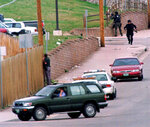 FILE - In this April 20, 1999, file photo, SWAT members run down Pierce Street while a Jefferson County, Colo., Sheriff's Department deputy peers through a fence to keep an eye on Columbine High School after a pair of gunmen went on a shooting rampage inside the facility in Littleton, Colo. (AP Photo/David Zalubowski, File)
