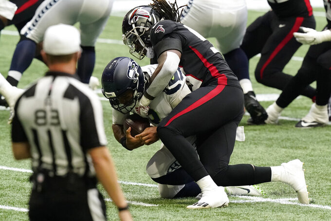 Atlanta Falcons defensive end Takkarist McKinley (98) sacks Seattle Seahawks quarterback Russell Wilson (3) during the first half of an NFL football game, Sunday, Sept. 13, 2020, in Atlanta. (AP Photo/Brynn Anderson)