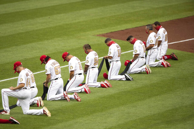 Members of Washington Nationals kneel and hold a piece of black fabric before an opening day baseball game against the New York Yankees at Nationals Park, Thursday, July 23, 2020, in Washington. (AP Photo/Alex Brandon)
