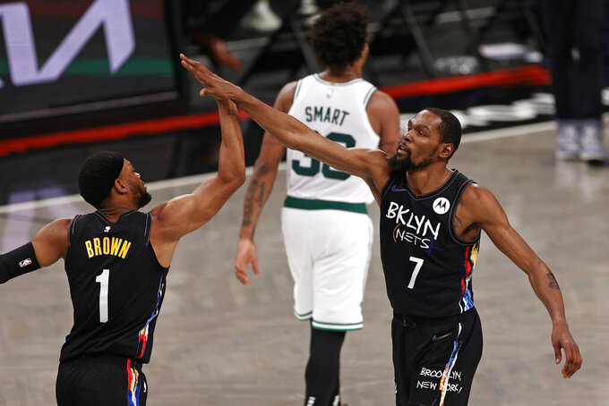 Brooklyn Nets forward Kevin Durant (7) high-fives Bruce Brown as Boston Celtics guard Marcus Smart walks off the court in the second half of Game 5 during an NBA basketball first-round playoff series, Tuesday, June 1, 2021, in New York. (AP Photo/Adam Hunger)