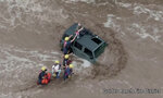 This drone image provided by the Golder Ranch Fire District shows firefighters safely rescue a man and his two daughters from the roof of their vehicle after it was swept away in fast moving water just north of Tucson, Ariz., on Wednesday, July 14, 2021. (Golder Ranch Fire District via AP)
