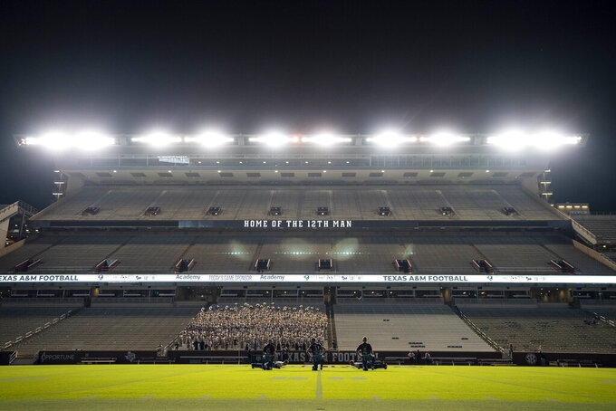 The Texas A&M University Yell Leaders kneel at midfield as part of the first Midnight Yell Practice this season in Kyle Field, College Station, Texas early Saturday, Sept. 26, 2020. Due to Coronavirus restrictions, the Texas A&M Band were the only crowd allowed in the normally packed stands for the traditional game day event in College Station, Texas. (Sam Craft/Texas A&M University via AP, Pool)