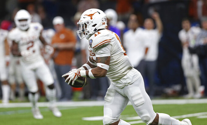 Texas defensive back P.J. Locke III (11) pulls in an interception of a Georgia pass during the second half of the Sugar Bowl NCAA college football game in New Orleans, Tuesday, Jan. 1, 2019. (AP Photo/Rusty Costanza)