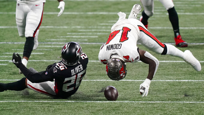 Tampa Bay Buccaneers wide receiver Chris Godwin (14) and Atlanta Falcons cornerback Isaiah Oliver (26) collide during the first half of an NFL football game, Sunday, Dec. 20, 2020, in Atlanta. (AP Photo/Brynn Anderson)