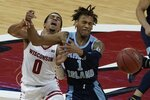 Rhode Island's Fatts Russell tries to steal the ball from Wisconsin's D'Mitrik Trice during the second half of an NCAA college basketball game Wednesday, Dec. 9, 2020, in Madison, Wis. Wisconsin won 73-62. (AP Photo/Morry Gash)