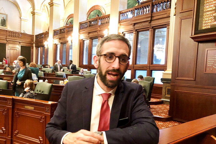 State Rep. Will Guzzardi, D-Chicago, speaks to reporters on the floor of the Illinois House in Springfield, Illinois, on Wednesday, Nov. 13, 2019, after the House voted 100-13 to limit out-of-pocket costs for prescription insulin to $100 a month. The Senate has approved the idea in answer to skyrocketing insulin costs but a change in the House version requires another Senate vote. (AP Photo by John O'Connor)