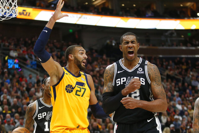 Utah Jazz center Rudy Gobert (27) reacts after fouling San Antonio Spurs forward LaMarcus Aldridge, right, during the first half of an NBA basketball game Friday, Feb. 21, 2020, in Salt Lake City. (AP Photo/Rick Bowmer)