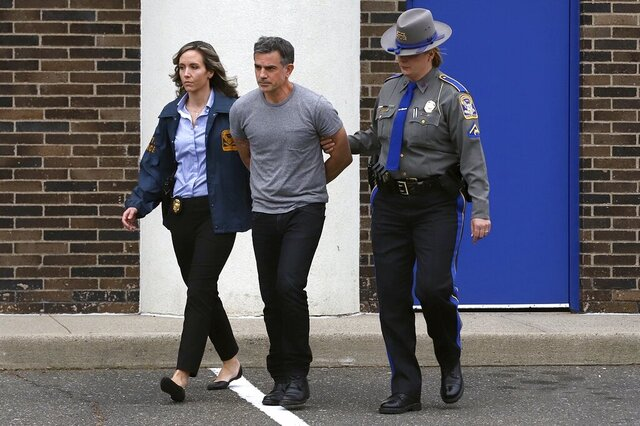 Connecticut State Police officers lead Fotis Dulos, center, from the State Police barracks to a waiting car Tuesday, Jan. 7, 2020, in Bridgeport, Conn., after he was arrested at his home in Farmington. He faces charges he murdered his estranged wife Jennifer Dulos, who went missing in May 2019. (AP Photo/Chris Ehrmann)