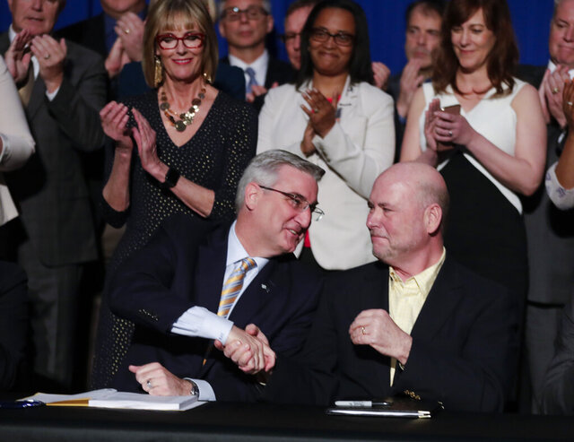 FILE - In this April 29, 2019 file photo, Indiana Gov. Eric Holcomb, left, shakes hands with Speaker of the House Brian Bosma, R-Indianapolis after signing the state's budget bill at the Statehouse in Indianapolis. The 2020 Indiana legislative session begins Monday.(AP Photo/Michael Conroy,File)
