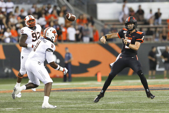 Oregon State quarterback Jake Luton throws a pass past Oklahoma State linebacker Amen Ogbongbemiga (11) during the first half of an NCAA college football game in Corvallis, Ore., Friday, Aug. 30, 2019. (AP Photo/Amanda Loman)