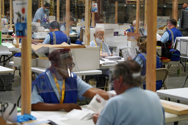FILE - In this June 9, 2020 file photo election workers process mail-in ballots during a nearly all-mail primary election in Las Vegas. The Trump campaign and Nevada Republicans want a state judge to stop the counting of Las Vegas-area mail-in ballots, alleging that