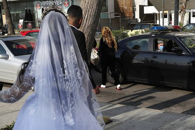 FILE - In this April 18, 2020 file photo, a policeman asks a bride and groom to leave the waterfront promenade where they had decided to take some pictures, in Beirut, Lebanon. In a region where marriage is the cornerstone of society, couples are plowing ahead with weddings, despite the deadly risks. From the Palestinian territories to the United Arab Emirates, officials attribute a spike in coronavirus cases to traditional, large-scale weddings that flout public health restrictions. (AP Photo/Hussein Malla, File)