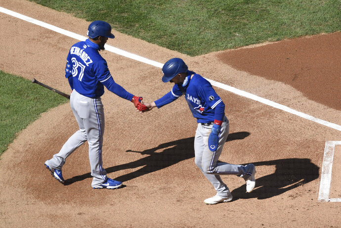 Toronto Blue Jays' Cavan Biggio, right, scores on a balk and is greeted by Teoscar Hernandez during the first inning of a baseball game against the Philadelphia Phillies, Sunday, Sept. 20, 2020, in Philadelphia. (AP Photo/Michael Perez)