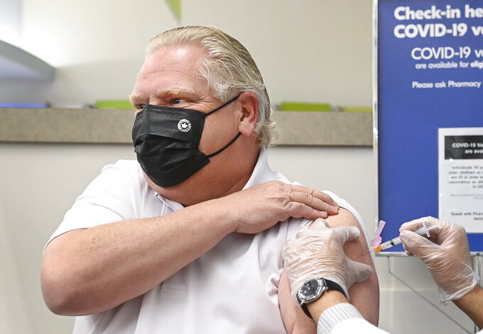 Ontario Premier Doug Ford, left, receives the Astrazeneca-Oxford COVID-19 vaccine from pharmacist Anmol Soor at Shoppers Drug Mart during the COVID-19 pandemic in Toronto on Friday, April 9, 2021. (Nathan Denette/The Canadian Press via AP)
