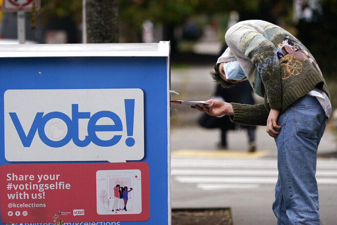 A voter turns sideways as he eyes the opening of a ballot drop box before placing his ballot inside it Wednesday, Oct. 28, 2020, in Seattle. Washington state is one of five states, along with Colorado, Hawaii, Oregon, and Utah, that conduct elections entirely by mail-in voting. (AP Photo/Elaine Thompson)