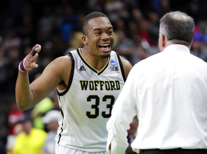 Wofford's Cameron Jackson (33) greets coach Mike Young as he comes off the court during the final moments against Seton Hall during a first-round game in the NCAA men's college basketball tournament in Jacksonville, Fla., Thursday, March 21, 2019. (AP Photo/John Raoux)