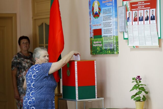 A woman casts her ballot at a polling station during a early voting ahead of Sunday's election in the western city of Lida, Belarus, Friday, Aug. 7, 2020. Belarus' authoritarian President Alexander Lukashenko faces a perfect storm as he seeks a sixth term in Sunday's election after 26 years in office. (AP Photo/Sergei Grits)
