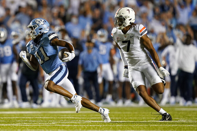 North Carolina wide receiver Josh Downs (11) runs the ball as Virginia outside linebacker Noah Taylor (7) chases during the first half of an NCAA college football game in Chapel Hill, N.C., Saturday, Sept. 18, 2021. (AP Photo/Gerry Broome)