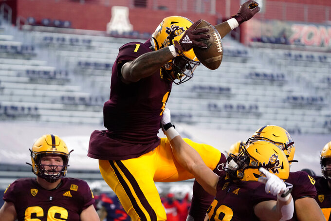 Arizona State running back DeaMonte Trayanum (1) celebrates with Case Hatch after scoring a touchdown against Arizona during the first half of an NCAA college football game Friday, Dec. 11, 2020, in Tucson, Ariz. (AP Photo/Rick Scuteri)