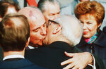 FILE -- In this Oct. 6, 1989 file photo, Soviet President Mikhail Gorbachev, left, kisses East German leader Erich Honecker after Gorbachev's arrival at East Berlin. At right is Raisa Gorbachev. (AP-Photo/Boris Yurchenko)