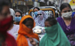 Indians wearing face masks as a precaution against the coronavirus walk at a market in Jammu, India, Monday, Aug 10, 2020. India is the third hardest-hit country by the pandemic in the world after the United States and Brazil. (AP Photo/Channi Anand)