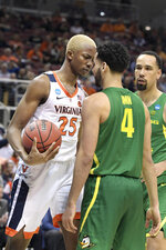 Virginia's Mamadi Diakite (25) and Oregon's Ehab Amin (4) face off during the second half of a men's NCAA Tournament college basketball South Regional semifinal game, Thursday, March 28, 2019, in Louisville, Ky. Virginia won 53-49. (AP Photo/Timothy D. Easley)