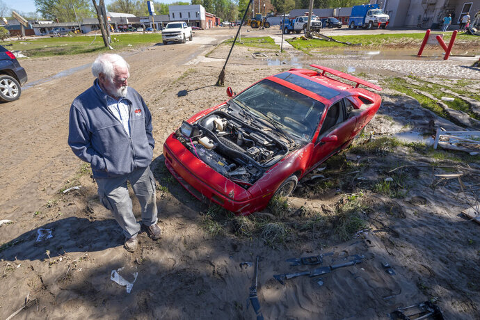 Tim Evans, owner of Fieros Forever, inspects the damage to his Lamborghini Diablo kit car that lay in a muddy ditch near downtown Sanford, Mich., Thursday, May 21, 2020. Evans lost several vehicles due to flooding that occurred after the Sanford dam failed earlier in the week.   (David Guralnick/Detroit News via AP)