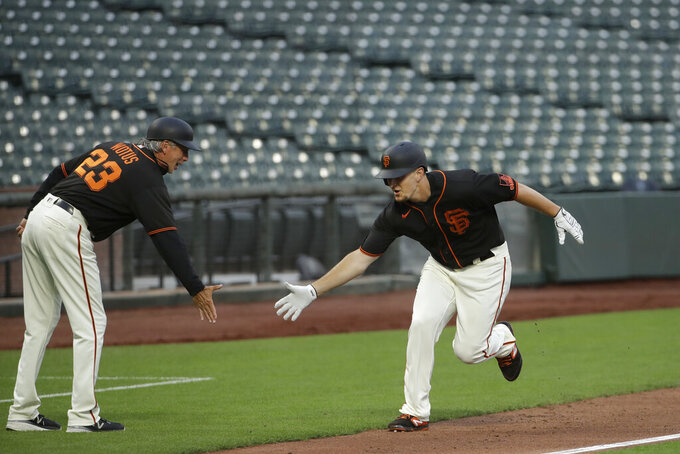San Francisco Giants' Alex Dickerson, right, celebrates with third base coach Ron Wotus after hitting a home run off of Oakland Athletics pitcher Mike Fiers during the second inning of an exhibition baseball game in San Francisco, Tuesday, July 21, 2020. (AP Photo/Jeff Chiu)