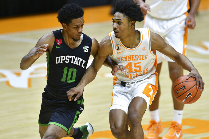 Tennessee's Keon Johnson (45) is guarded by South Carolina-Upstate's Tommy Bruner (10) during an NCAA college basketball game Wednesday, Dec. 23, 2020, in Knoxville, Tenn. (Saul Young/Knoxville News Sentinel via AP, Pool)