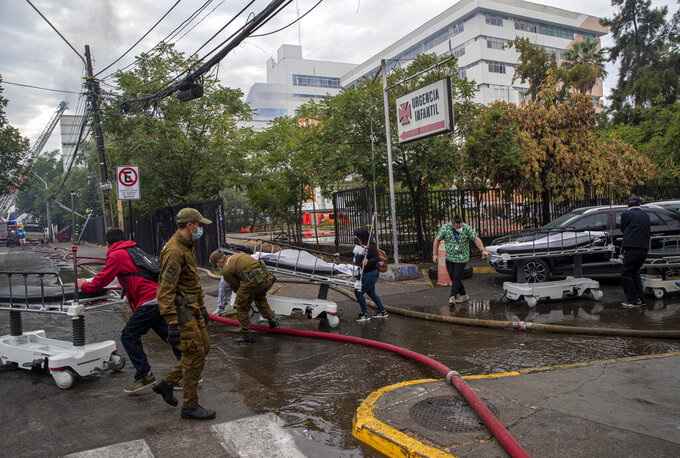 Healthcare workers push hospital beds outside the San Borja Arriaran hospital in Santiago, Chile, Saturday, Jan. 30, 2021, where a fire broke out in a boiler room. The fire forced the evacuation of more than 300 patients from the downtown hospital in Chile's capital on Saturday, but officials reported no injuries. (AP Photo/Esteban Felix)
