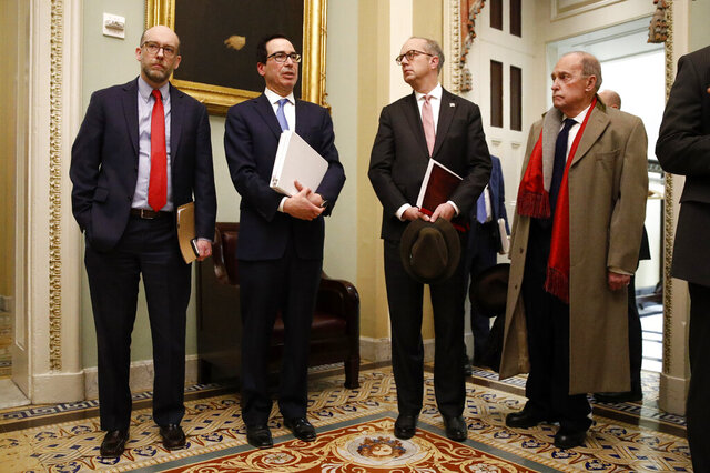 Treasury Secretary Steve Mnuchin, second from left, speaks with members of the media as he departs a meeting with Senate Republicans on an economic lifeline for Americans affected by the coronavirus outbreak. on Capitol Hill in Washington, Monday, March 16, 2020. Standing with Mnuchin is White House chief economic adviser Larry Kudlow, right. (AP Photo/Patrick Semansky)