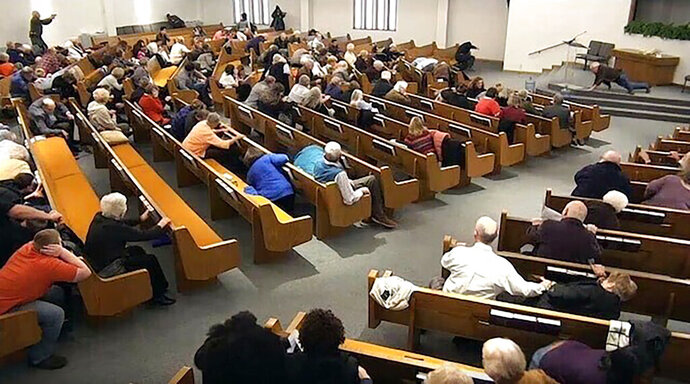 In this still frame from livestreamed video provided by law enforcement, churchgoers take cover while a congregant armed with a handgun, top left, engages a man who opened fire, near top center just right of windows, during a service at West Freeway Church of Christ, Sunday, Dec. 29, 2019, in White Settlement, Texas. The footage was broadcast online by the church according to a law enforcement official, who provided the image to The Associated Press on condition on anonymity because the investigation is ongoing. (West Freeway Church of Christ/Courtesy of Law Enforcement via AP)