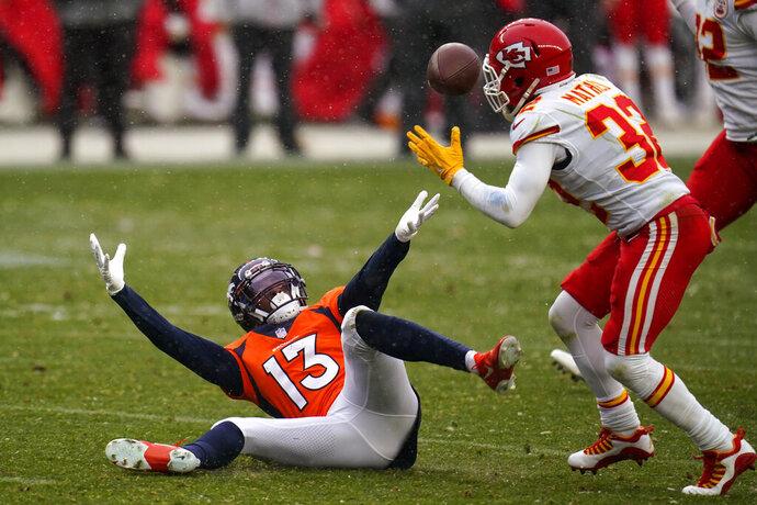 Denver Broncos wide receiver K.J. Hamler (13) falls as Kansas City Chiefs strong safety Tyrann Mathieu intercepts a pass during the second half of an NFL football game Sunday, Oct. 25, 2020, in Denver. (AP Photo/Jack Dempsey)