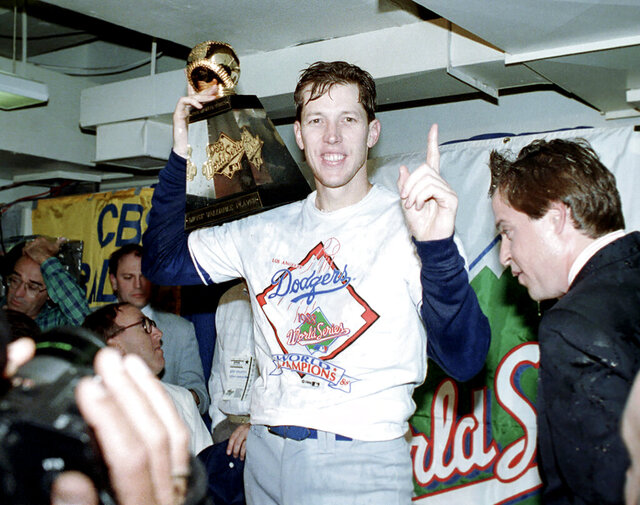 FILE - In this Oct. 20, 1988, file photo, Los Angeles Dodgers pitcher Orel Hershiser holds his World Series Most Valuable Player trophy following the Dodgers' decisive 5-2 win over the Oakland Athletics in Oakland, Ca. Since Hershiser struck out Oakland's Tony Phillips for the final out of the 1988 World Series, the Dodgers have played 5,014 regular-season games and 113 more in the postseason in pursuit of their next title. They have spent $3.69 billion in player payroll over 32 seasons. One more win and that elusive seventh championship will be theirs. (AP Photo/Lennox McLendon, File)