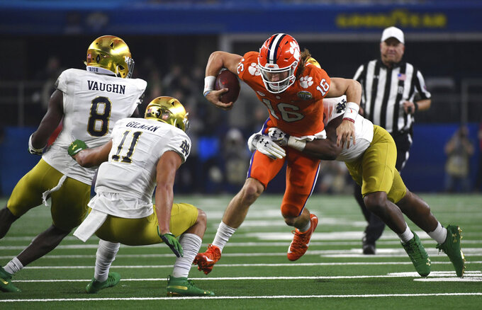 Notre Dame cornerback Donte Vaughn (8), safety Alohi Gilman (11) and defensive lineman Justin Ademilola combine to stop Clemson quarterback Trevor Lawrence (16) from gaining extra yardage on a running play in the first half of the NCAA Cotton Bowl semi-final playoff football game, Saturday, Dec. 29, 2018, in Arlington, Texas. (AP Photo/Jeffrey McWhorter)