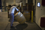 An employee moves an empty barrel in the shipping warehouse of the French wine producer MDCV, in the Chateau des Bertrands in Le Cannet-des-Maures, in the Provence region, Thursday Oct. 10, 2019. European producers of premium specialty agricultural products like those protected at home for their territorial origin and sometimes centuries of artisanal know-how that fetch premium prices like French wine, are facing a U.S. tariff hike on Friday, dragged into a trade war over the fiercely competitive aerospace industry.(AP Photo/Daniel Cole)