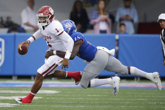 Oklahoma quarterback Jalen Hurts (1) is tackled by Kansas linebacker Kyron Johnson (15) during the first half of an NCAA college football game Saturday, Oct. 5, 2019, in Lawrence, Kan. (AP Photo/Charlie Riedel)
