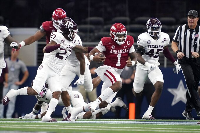 Arkansas quarterback KJ Jefferson (1) finds running room as Texas A&M defensive back Antonio Johnson (27) and linebacker Edgerrin Cooper (45) give chase in the first half of an NCAA college football game in Arlington, Texas, Saturday, Sept. 25, 2021. (AP Photo/Tony Gutierrez)