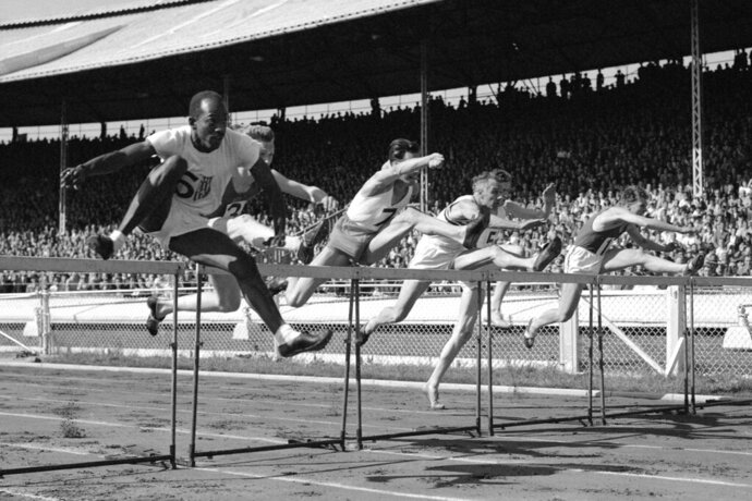 FILE - In this June 1949 photo, competitors jump in the 120-yard international hurdles during the British Games, incorporating International Athletics Match, in London. The competitors are P Van de Sype of Belgium (1); A. Marie of France (no.3); Donald Finlay of Britain (4); E. Arneberg, of Norway (5); Harrison Dillard, left, of the United States, and G. V. D. Hoeven, of Holland (7). Dillard won the event in 14.4 seconds, followed by A. Marie in second place and Finlay in third. Dillard, the only Olympic runner to win gold medals in both the sprints and high hurdles, has died. He was 96. Longtime friend Ted Theodore said Dillard died Friday, Nov. 15, 2019, at the Cleveland Clinic after a fight with stomach cancer. The 1955 Sullivan Award winner as the nation's outstanding amateur athlete, Dillard was the oldest living U.S. Olympic champion. (AP Photo, File)