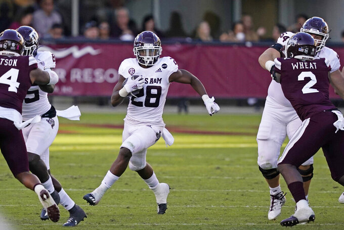 Texas A&M running back Isaiah Spiller (28) runs upfield past Mississippi State linebacker Tyrus Wheat (2) during the second half of an NCAA college football game in Starkville, Miss., Saturday, Oct. 17, 2020.  (AP Photo/Rogelio V. Solis)