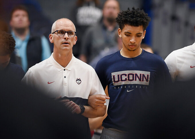 Connecticut's James Bouknight, right, locks arms with Connecticut head coach Dan Hurley during the national anthem before an exhibition NCAA college basketball game against Saint Michael's, Wednesday, Oct. 30, 2019, in Hartford, Conn. (AP Photo/Jessica Hill)