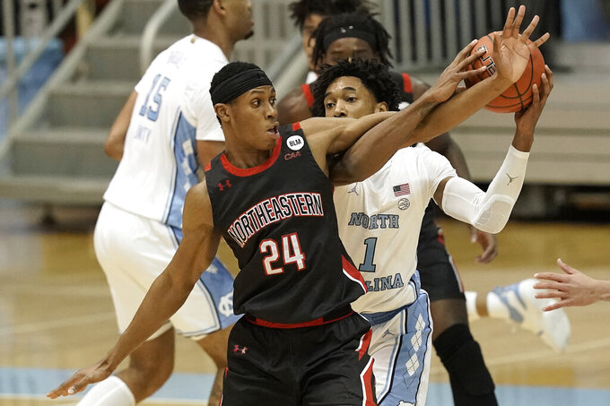 Northeastern guard Shaquille Walters (24) reaches for the ball against North Carolina guard Leaky Black (1) during the second half of an NCAA college basketball game in Chapel Hill, N.C., Wednesday, Feb. 17, 2021. (AP Photo/Gerry Broome)