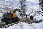 Workers with heavy machinery clear a snow-covered road in Keran, a small town in Neelum Valley, Pakistan-administered Kashmir, Tuesday, Jan. 14, 2020. Severe winter weather has claimed more lives as avalanches triggered by heavy snowfall killed more than 50 people in Pakistan-administered Kashmir while a dozen died in neighboring Afghanistan, officials said Tuesday. (AP Photo/M.D. Mughal)