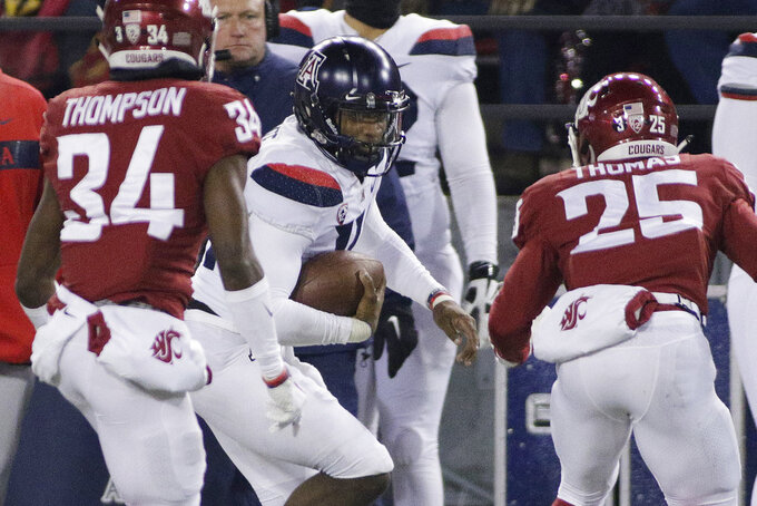 Arizona quarterback Khalil Tate, center, runs with the ball while pursued by Washington State safety Skyler Thomas (25) and safety Jalen Thompson (34) during the first half of an NCAA college football game in Pullman, Wash., Saturday, Nov. 17, 2018. (AP Photo/Young Kwak)