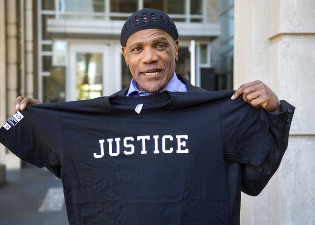 """In this March 21, 2019, photo, Archie Williams, who had been serving a life sentence after conviction for a 1983 rape, holds a T-shirt given to him after he walked out of the 19th Judicial District Courthouse in Baton Rouge, La., a free man, after a hearing in which he was exonerated after fingerprint technology pointed to another suspect decades after his conviction. Williams fulfilled one of his biggest dreams: singing on """"America's Got Talent."""" The NBC reality competition's latest season premiered May 26, 2020, with Williams among the contestants. (Travis Spradling/The Advocate via AP)"""