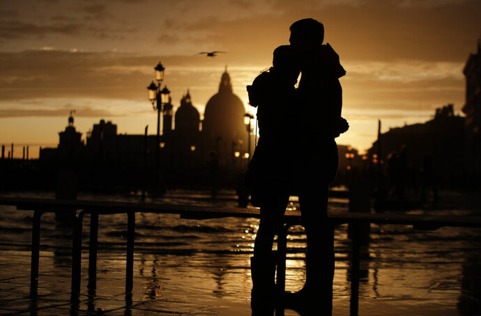In this photo taken on Sunday, Nov. 17, 2019, a couple stands in a golden sunset in Venice, Italy. Venetians are fed up with what they see as an inadequate to the city's mounting problems: record-breaking flooding, damaging cruise ship traffic and over-tourism. They feel largely left to their own devices, and with ever fewer Venetians living in the historic part of the city to defend its interests and keep it from becoming a theme park or museum. (AP Photo/Luca Bruno)
