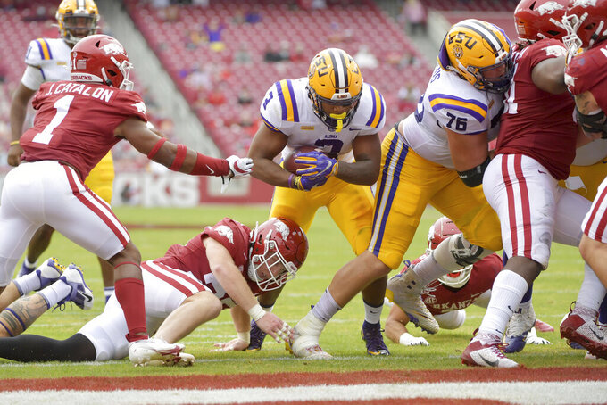 LSU running back Tyrion Davis-Price (3) finds a hole in the Arkansas defense as he runs for a touchdown during the first half of an NCAA college football game Saturday, Nov. 21, 2020, in Fayetteville, Ark. (AP Photo/Michael Woods)