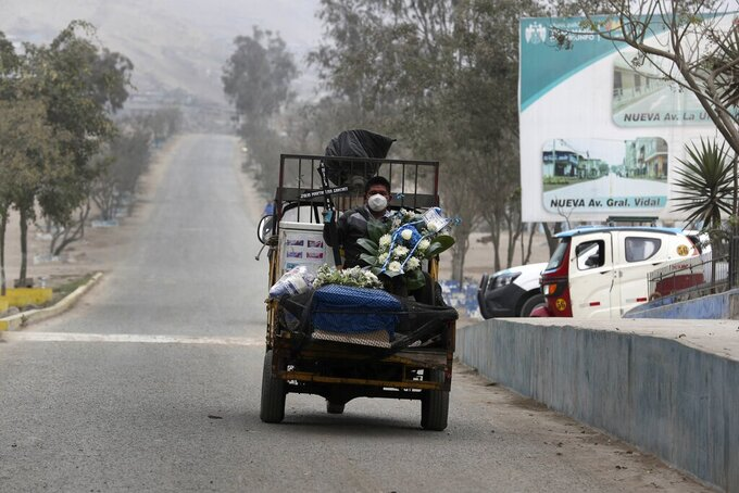 Robert Liza holds a cross and flowers as he sits on his family's ice cream truck carrying the coffin of his father Martin Liza, who he said died Tuesday of complications related to COVID-19, upon entry to the Nueva Esperanza cemetery on the outskirts of Lima, Peru, Friday, Aug. 28, 2020, after the police spoke to the cemetery security guards to let them in. Liza said he doesn't have the money to bury his 70-year-old father, and that he and his brother have slept for two nights alongside the coffin outside the cemetery in hopes the cemetery will let them bury their father for free. (AP Photo/Martin Mejia)