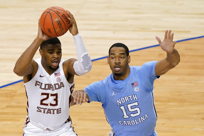 Florida State guard M.J. Walker (23) looks for help as North Carolina forward Garrison Brooks (15) pressures during the first half of an NCAA college basketball game in the semifinal round of the Atlantic Coast Conference tournament in Greensboro, N.C., Friday, March 12, 2021. (AP Photo/Gerry Broome)