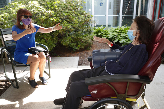 Marcie Abramson, left, gestures as she speaks to her mother, Cynthia, outdoors at the Hebrew Rehabilitation Center, Wednesday June 10, 2020, in Boston, under the state's new nursing home visitation guidelines which requires social distancing. The two haven't been able to visit in person since March. (AP Photo/Elise Amendola)
